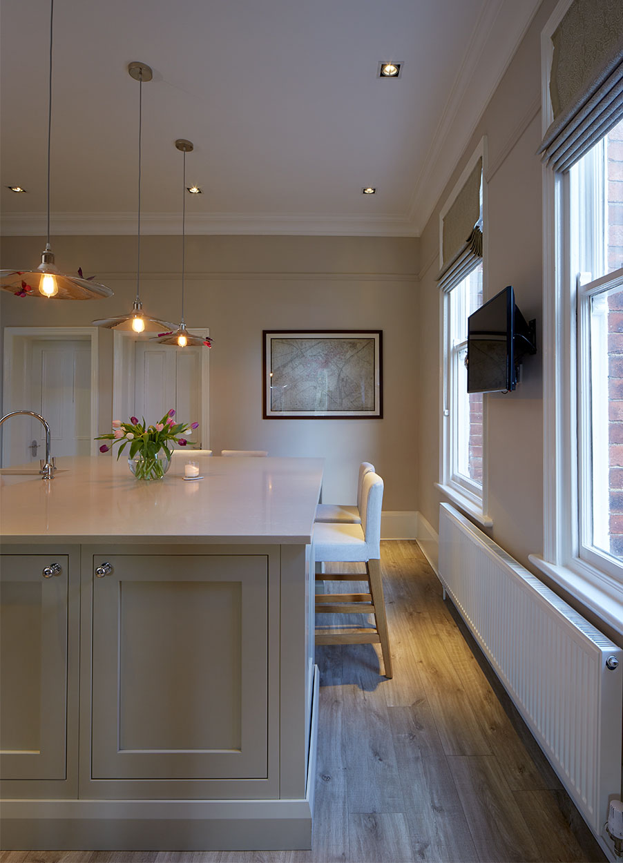 Marble island unit in neutral coloured kitchen.