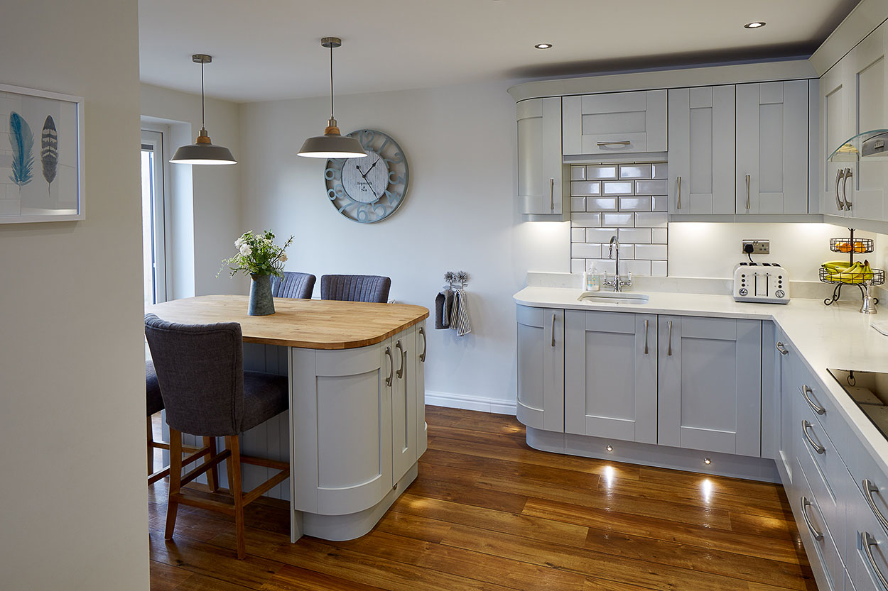 White with hardwood vanished worktop  and small breakfast bar.