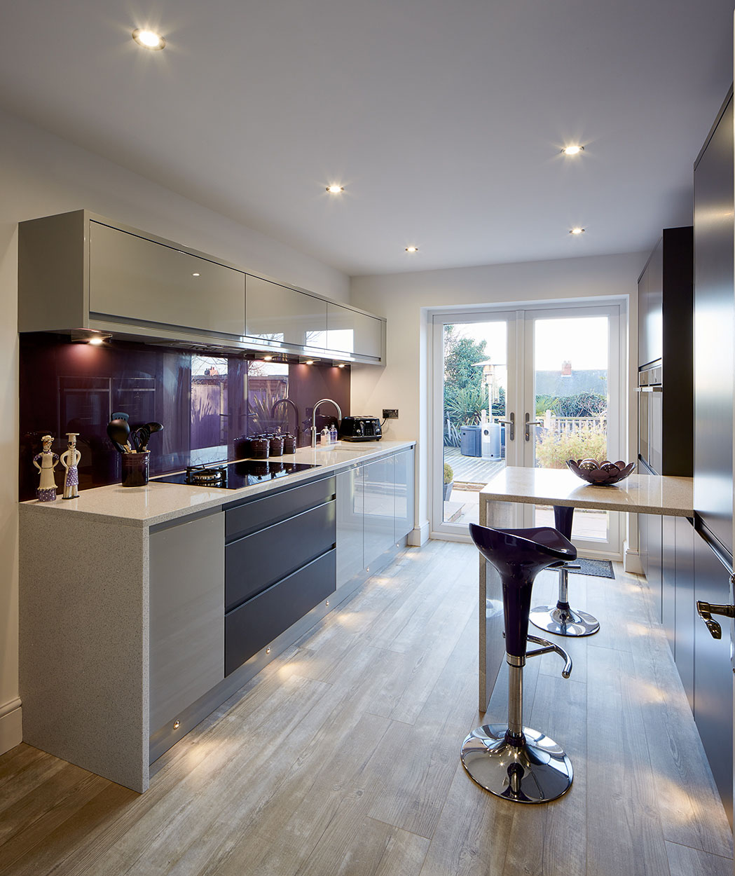 Panoramic view of white kitchen with a purple splashback.
