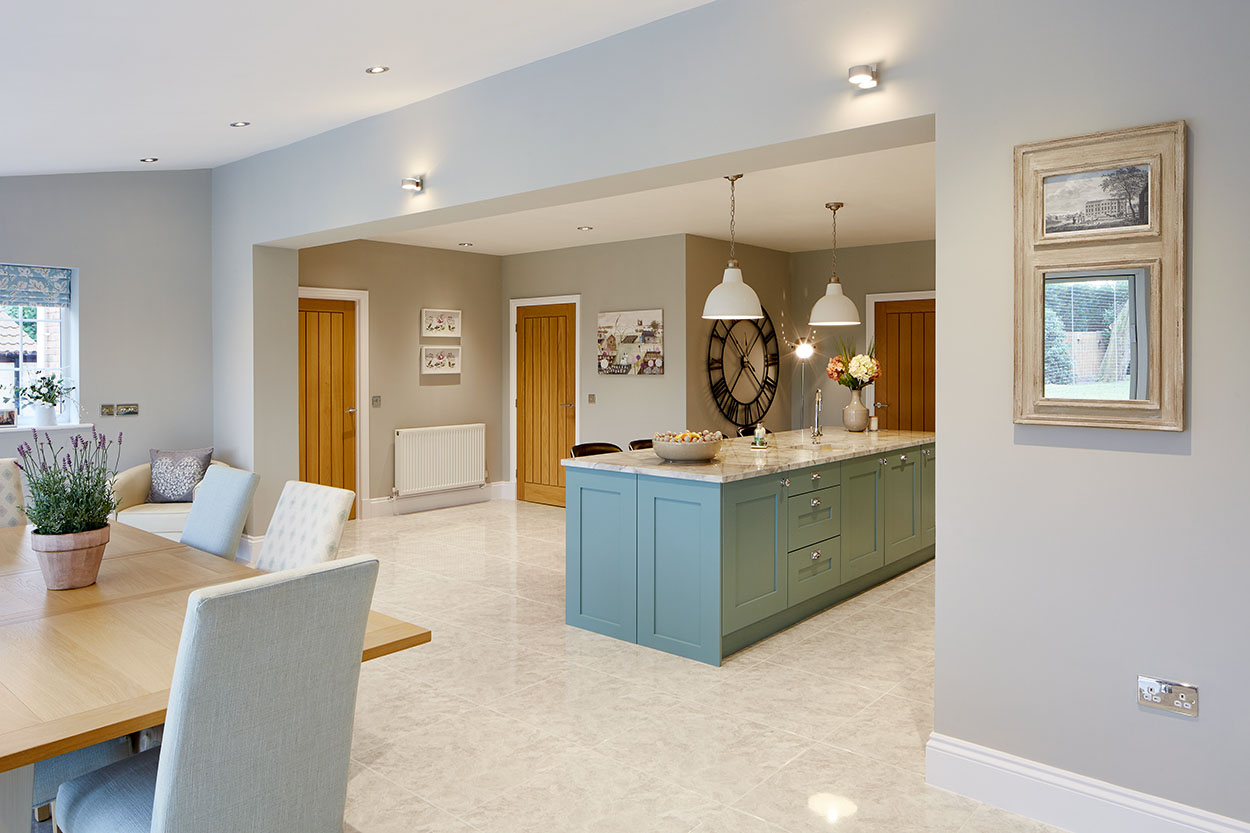 Open plan kitchen and living room with white fittings.